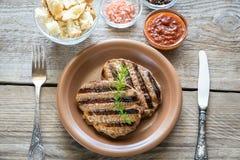 Nötköttbiffar på träbakgrunden Fotografering för Bildbyråer
