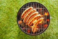 Nötköttbratwurst som grillar över en grillfestbrand Arkivfoto