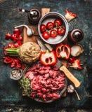 Nötköttgulasch av unga tjurar med grönsaker och matlagningingredienser, förberedelse på skärbräda och mörk lantlig bakgrund royaltyfri foto
