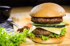 Nötkötthamburgare med ost och grönsaker Arkivfoton