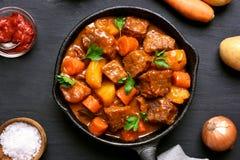 Nötköttkött som låtas småkoka med potatisar och morötter Arkivfoto