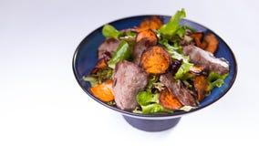 Nötköttsallad med sötpotatisar i blå kinesisk bunke på vitbac royaltyfri bild