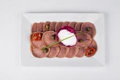 Nötkötttunga med pepparrot och stekte tomater på vit platta b Arkivfoto