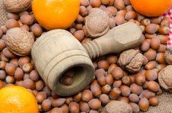Nötknäppare, hasselnötter, mandariner och valnötter på en säckvävpåse Fotografering för Bildbyråer