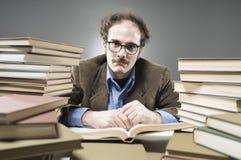 Nötliknande professor in - mellan en bunt av böcker royaltyfri fotografi