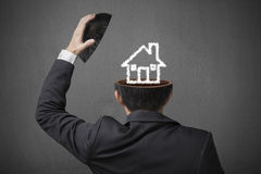 Núblese el dibujo de la casa dentro de la cabeza del hombre de negocios en el CCB gris del hormigón Fotos de archivo