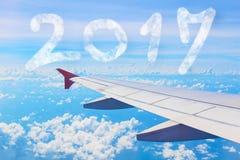 Núblese el número de la forma 2017 años sobre el aeroplano del ala en el cielo azul Imagen de archivo libre de regalías