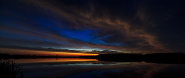 Núblese en el amanecer encendido cielo de la mañana, reflejado en el agua Imagen de archivo libre de regalías