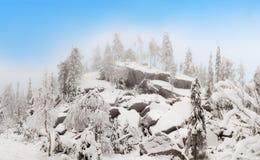 Núblese en las rocas arruinadas en bosque del invierno Imagenes de archivo