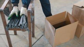 Núcleos da fibra de vidro - o trabalhador embala a produção na caixa no armazém video estoque