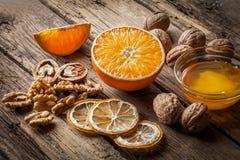 Núcleos da noz e nozes inteiras com laranja Fotografia de Stock
