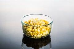 Núcleos de milho na bacia de vidro transparente no backg reflexivo escuro Foto de Stock Royalty Free