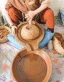 Núcleos de moedura do argão da mulher marroquina no líquido oleoso marrom grosso imagens de stock royalty free