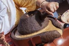 Núcleos de moedura do argão da mulher marroquina tradicional com moinhos Fotografia de Stock Royalty Free