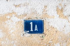 Número azul 1 A um do metal do endereço velho da casa do vintage na fachada do emplastro da parede exterior abandonada da casa no imagem de stock