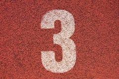 Número branco na pista de borracha vermelha, textura da trilha de pistas running no estádio exterior pequeno Imagens de Stock Royalty Free