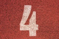Número branco na pista de borracha vermelha, textura da trilha de pistas running no estádio exterior pequeno Fotografia de Stock Royalty Free