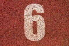 Número branco na pista de borracha vermelha, textura da trilha de pistas running no estádio exterior pequeno Imagem de Stock Royalty Free