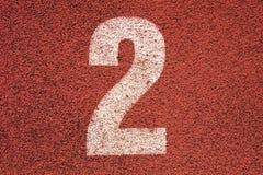 Número branco na pista de borracha vermelha, textura da trilha de pistas running no estádio exterior pequeno Fotos de Stock