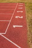 Número branco na pista de borracha vermelha, textura da trilha de pistas running no estádio exterior pequeno Foto de Stock