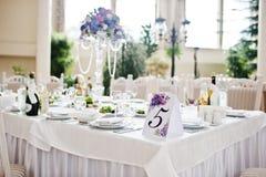 Número cinco na tabela para convidados no salão do casamento Foto de Stock