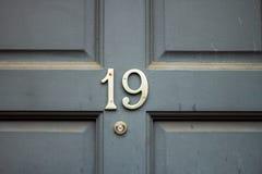 Número da casa 19 com o dezenove na prata em uma porta de madeira cinzenta fotos de stock royalty free