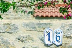 Número da casa dezesseis na parede de pedra na rua Imagens de Stock Royalty Free