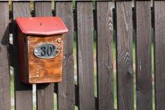 Número da casa 30 na caixa postal na cerca de madeira velha em uma vila remota fotografia de stock