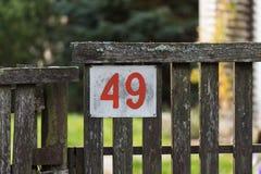 Número da casa 49 na cerca de madeira velha em uma vila remota foto de stock