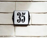 Número da casa preto e branco 35 na parede de tijolo Fotografia de Stock
