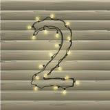 Número 2 da festão da luz de Natal em um fundo de madeira bonito Imagem de Stock Royalty Free