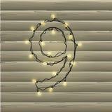 Número 9 da festão da luz de Natal em um fundo de madeira bonito Imagens de Stock Royalty Free