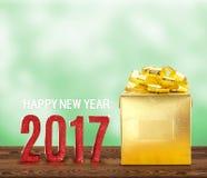 Número da madeira do ano novo feliz 2017 e presente dourado na madeira marrom Fotos de Stock
