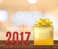 Número da madeira do ano novo feliz 2017 e presente dourado na madeira marrom Imagens de Stock