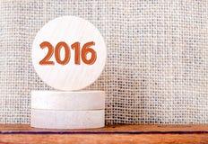 número de 2016 años en la madera redonda en la tabla con el backgroun marrón de la holgura Imagen de archivo