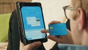 Número de cartão de crédito de enchimento do homem novo em sua tabuleta digital que paga pela compra em linha video estoque