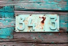 Número de casa aherrumbrado en la pared del verde del grunge Imagen de archivo libre de regalías