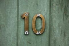 Número de cobre amarillo diez en puerta Foto de archivo libre de regalías