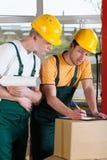 Número de comprobación de los trabajadores de Warehouse de cajas imagen de archivo