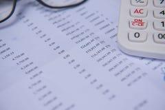 Número de cuentas del primer en un papel, una calculadora y vidrios impresos Imagenes de archivo