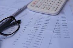Número de cuentas del primer en un papel, una calculadora y vidrios impresos Fotos de archivo libres de regalías