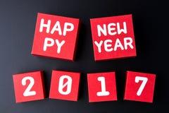Número de la Feliz Año Nuevo 2017 en los cubos rojos de la caja de papel en backg negro Fotos de archivo libres de regalías