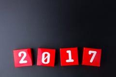 Número de la Feliz Año Nuevo 2017 en los cubos rojos de la caja de papel en backg negro Imagen de archivo libre de regalías
