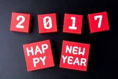 Número de la Feliz Año Nuevo 2017 en los cubos rojos de la caja de papel en backg negro Fotografía de archivo libre de regalías