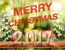 Número de la Feliz Navidad 2017 en la sobremesa de madera de Brown con el abstrac Foto de archivo