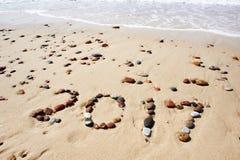 Número de las piedras mojadas 2017 en la playa de la arena Imágenes de archivo libres de regalías