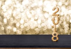 número de madera del Año Nuevo 2018 en la tabla de madera con el boke chispeante del oro Imágenes de archivo libres de regalías