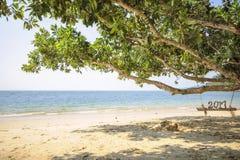 Número de madera 2017 en el oscilación de madera en fondo tropical de la playa Foto de archivo