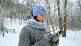 Número de marca de la mujer adulta en el teléfono en parque del invierno almacen de metraje de vídeo