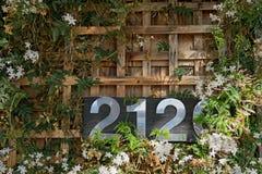 Número de matrícula 2120 de la casa del acero inoxidable en un fondo de madera Foto de archivo libre de regalías